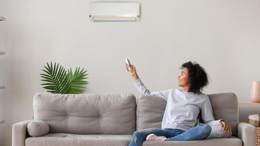 Smiling young African American woman using air conditioner, cooler system remote controller, switching, setting comfort temperature in living room, resting on cozy sofa at home, enjoy fresh air - Image.