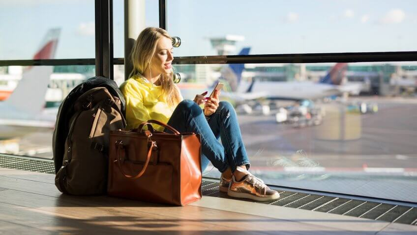 Woman sitting in airport and waiting for her flight, woman using phone in airport departure area.