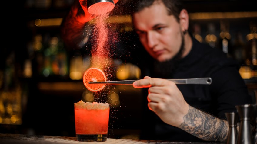 Tattooed professional bartender adding spices powder into a cocktail glass filled with a fresh strong alcoholic cocktail with slice of lemon.