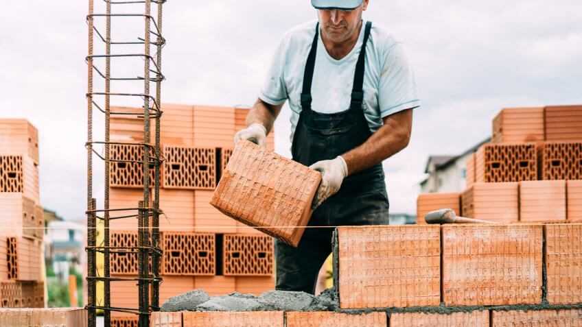 professional, portrait of industrial worker building walls with ceramic bricks.
