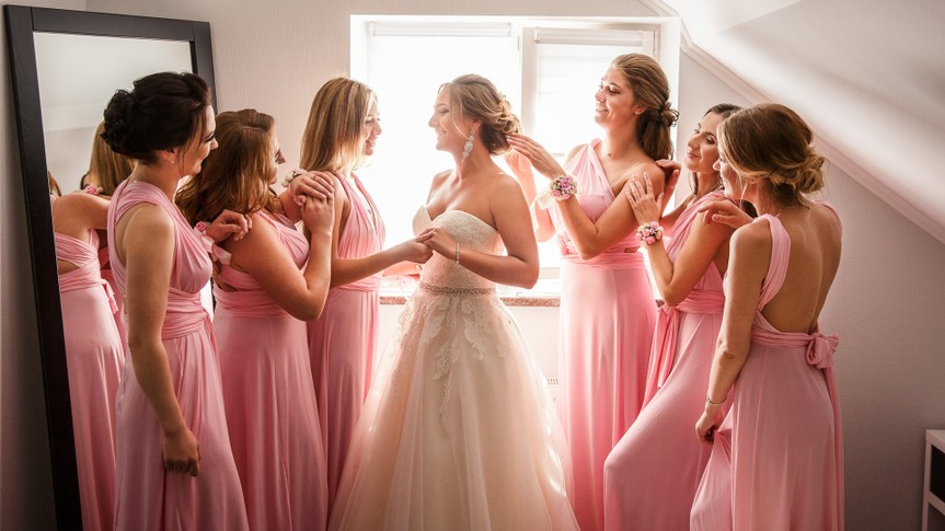 Bride with bridesmaids posing in hotel or fitting room at wedding day.