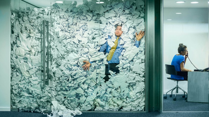 A businessman is trapped in his glass office by a surplus of discarded ideas on paper .