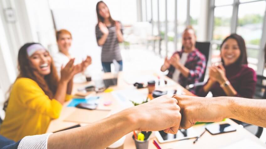 Business partners or coworkers fist bump in team meeting, multiethnic diverse group of happy colleagues clapping hands.