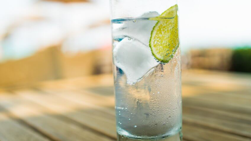Close up of a refreshing ice cold glass of water with a slice of lime.