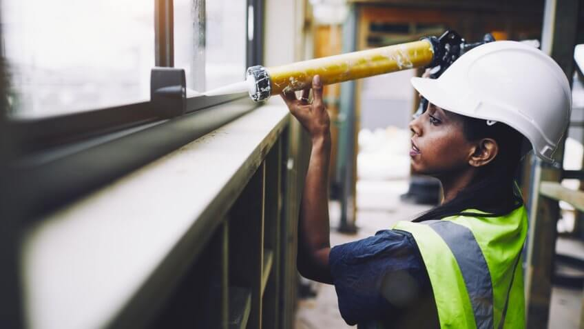 construction worker applying glue to a sill