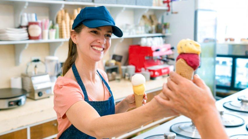 Female worker serving an ice cream to an unrecognizable customer at the ice cream parlor looking very happy and smiling.