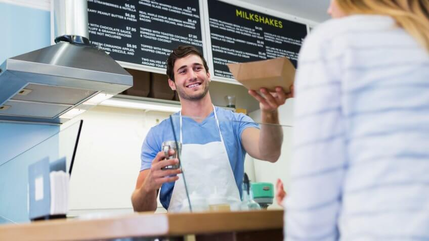 Young man (20s) working behind the counter of a shop selling gourmet waffles.