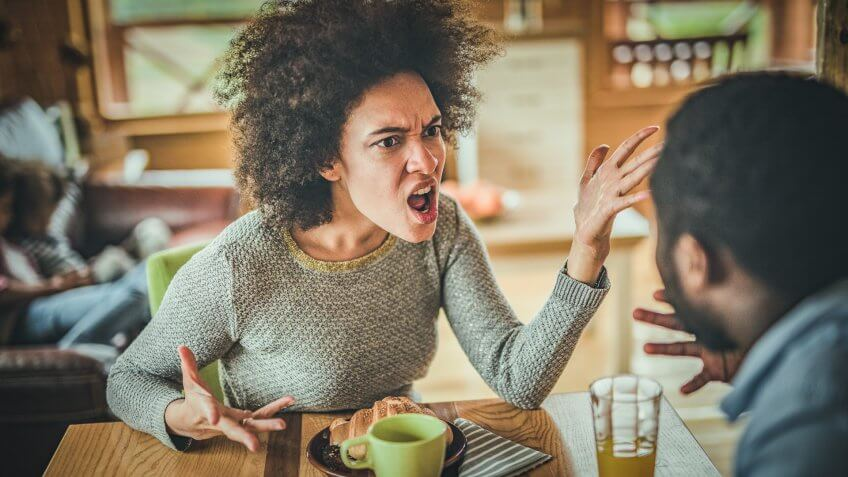 Young black couple arguing while having problems in their relationship at dining table.