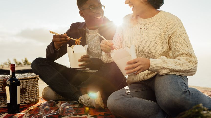 couple on picnic eating noodles and smiling on a sunny day.