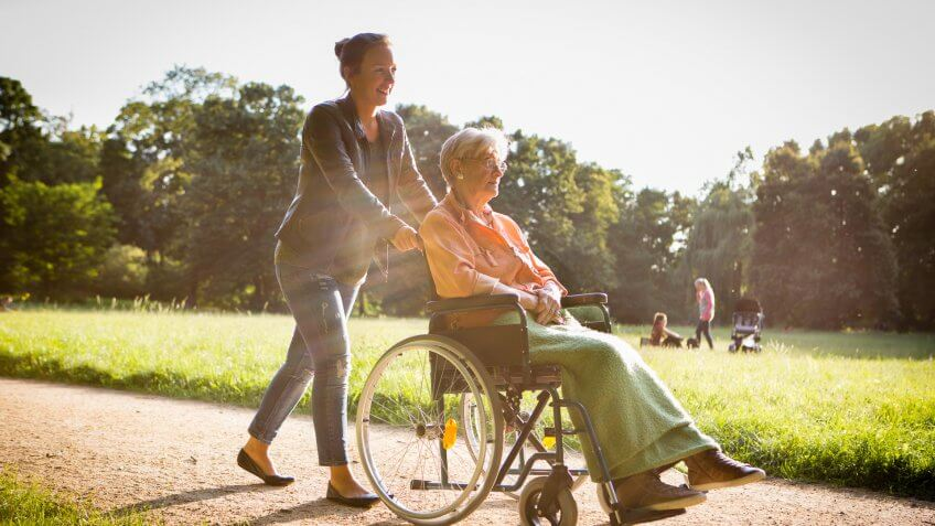 charming young woman pushing a senior woman in  a wheelchair through the park.