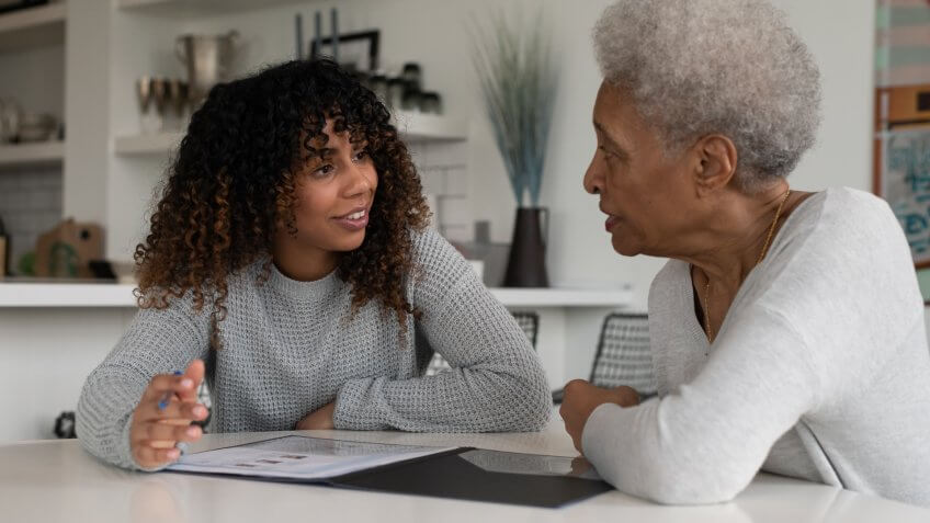 An ethnic female financial consultant is discussing strategy with an elder senior woman.