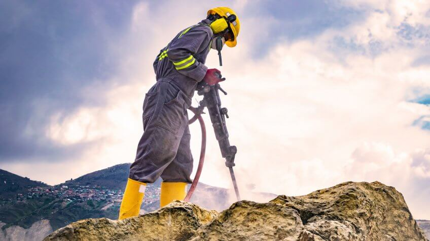 Worker with helmet and protective suit using a drilling machine on top of a large rock.