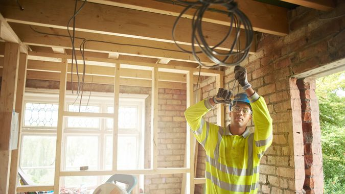 a young male carpenter clipping electrical wires on a first fix.