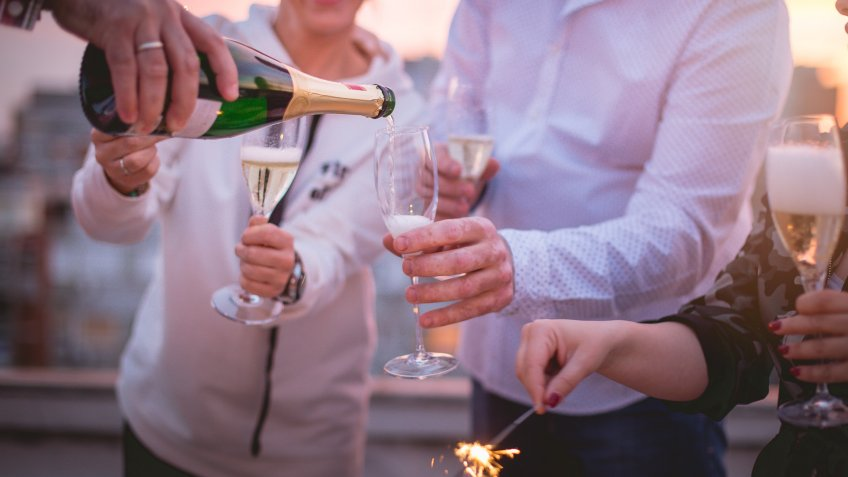 Close up of a group of four friends is on a roof top of a building, celebrating with champagne and sparklers.
