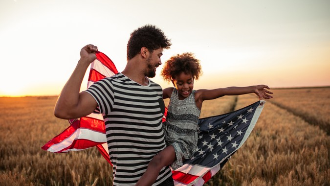 Father and daughter holding American flag.
