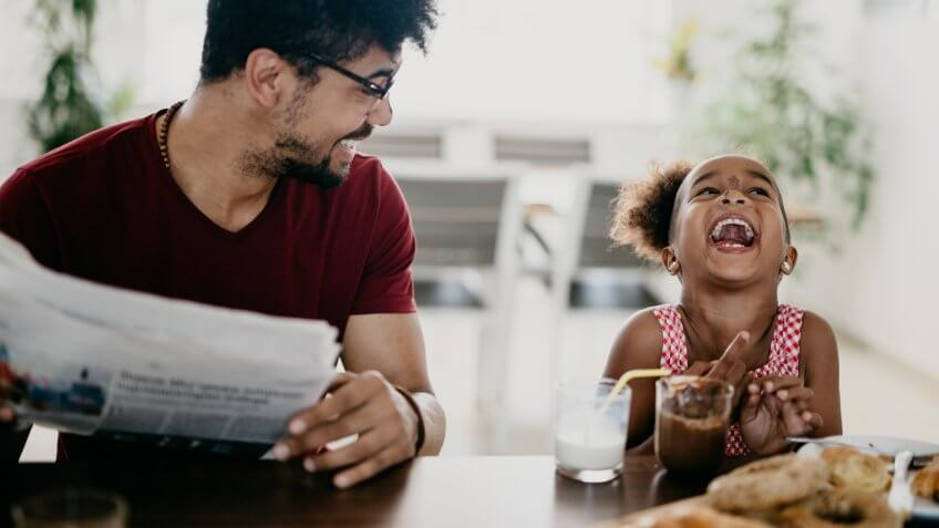 Little girl bursts into laugh while having breakfast with her father.