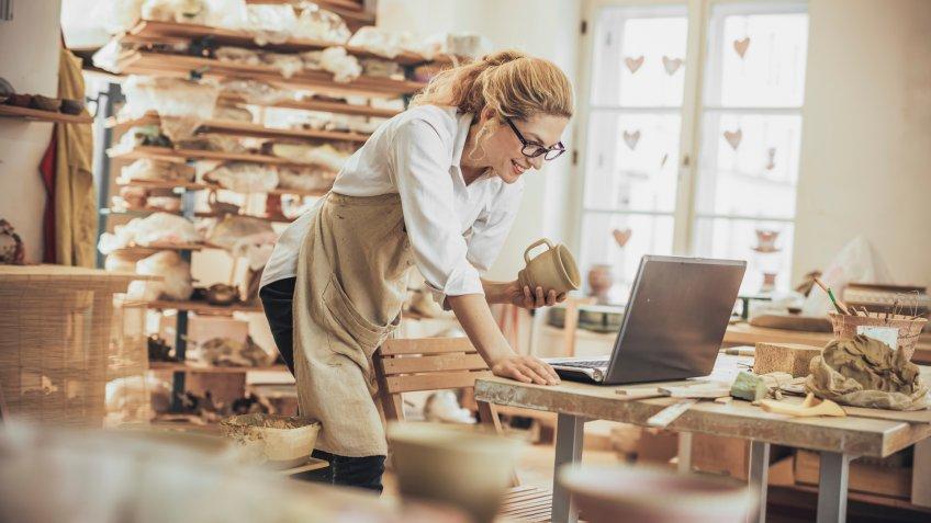 Potter entrepreneur using laptop  in workshop.