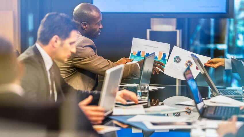 African American businessman showing infographic to his invisible colleague also holding infographic, on a board meeting at conference table.