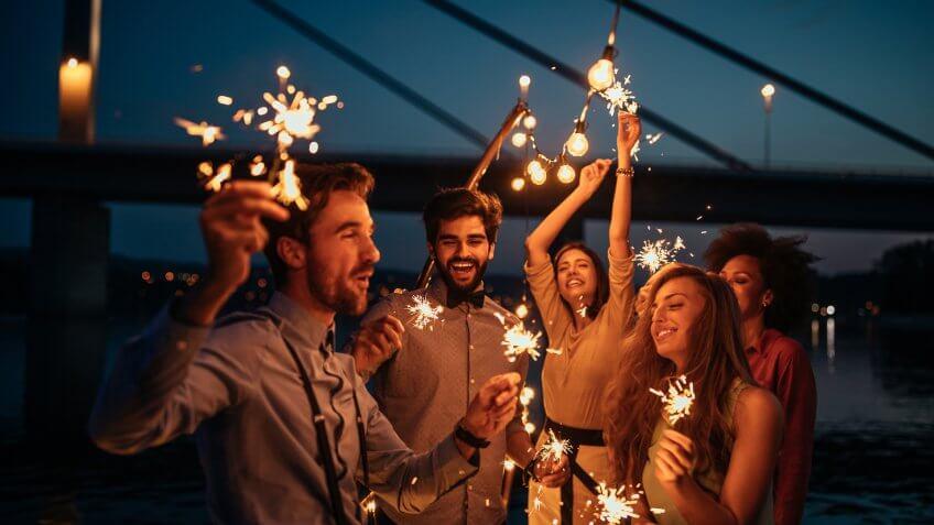 Group of friends celebrating holding sparklers.