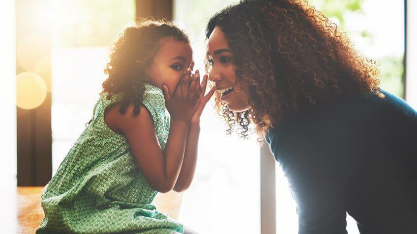 girl telling secret code to her mom