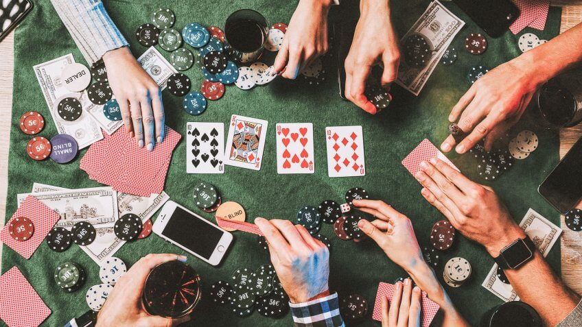 group of friends gambling with cards and poker chips