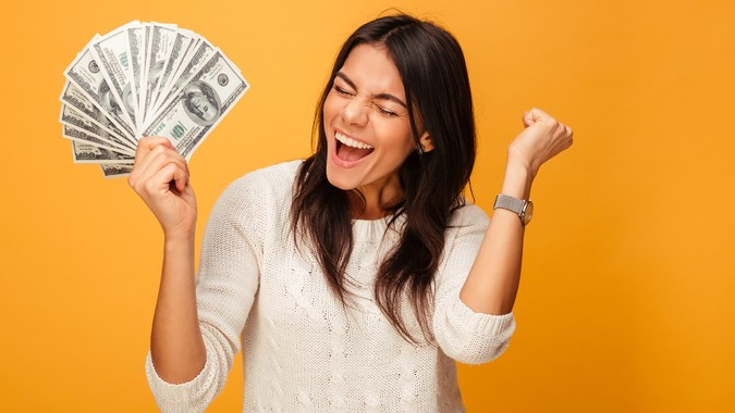 Portrait of a cheerful young woman holding money banknotes and celebrating isolated over yellow background - Image.