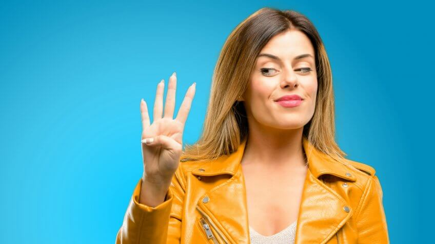 Beautiful young woman raising his finger, is the number four, blue background - Image.