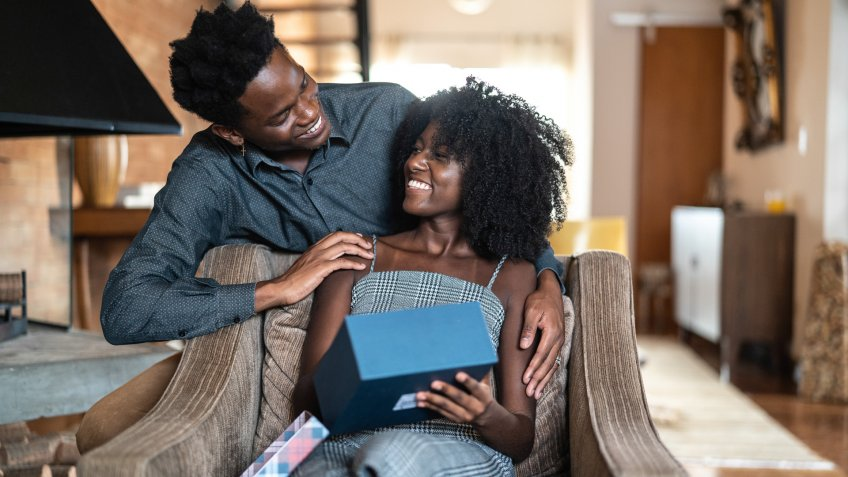 African descent brazilian couple exchanging gifts at home.