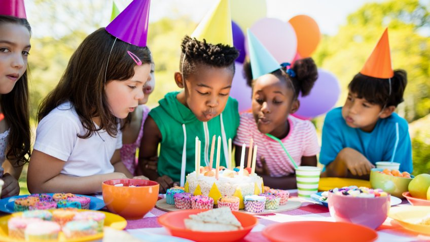 Cute children blowing together on the candle during a birthday party on a park.