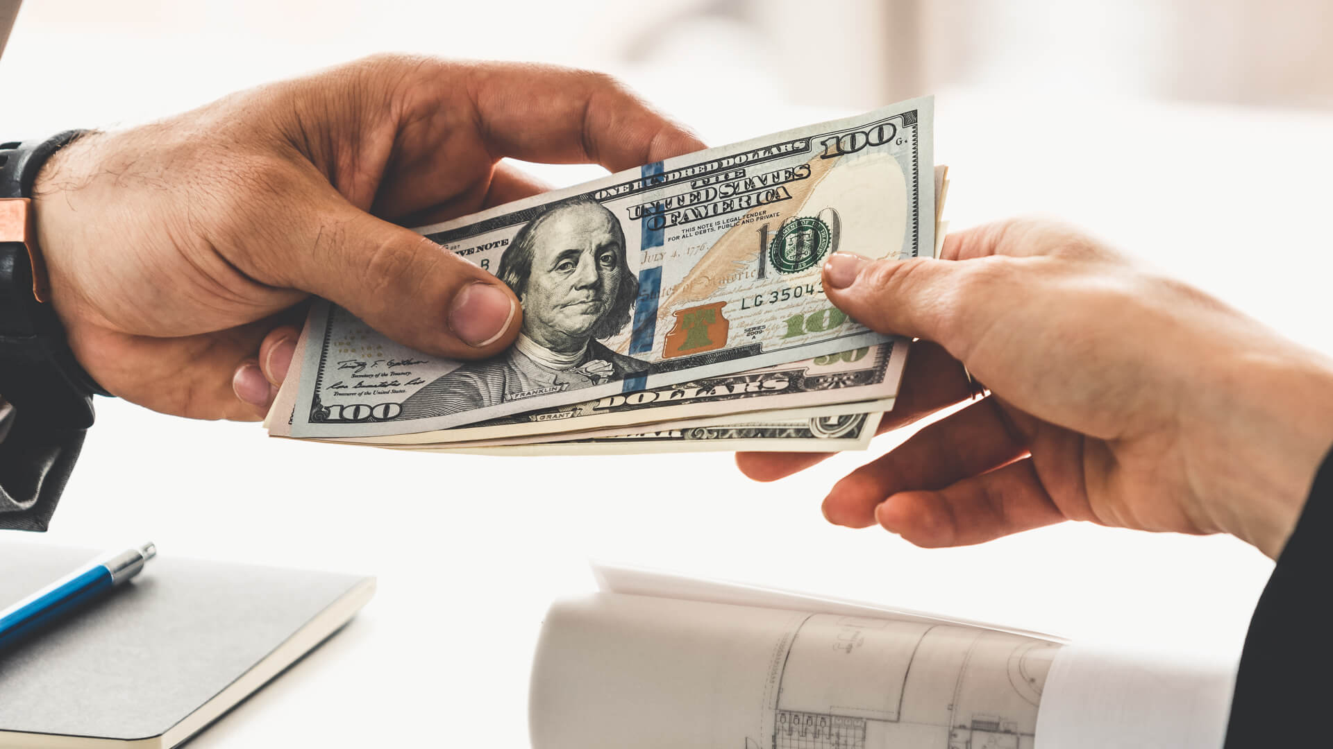 Businessman hand sending money to another business person.