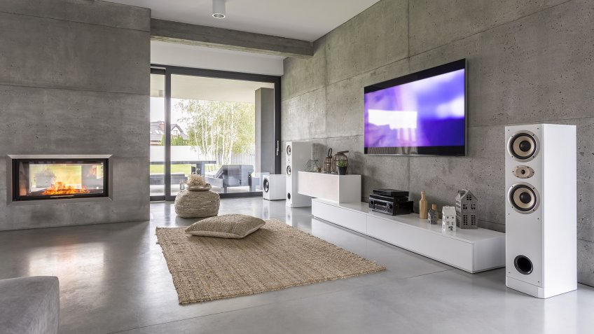Tv living room with window, fireplace and concrete wall effect.