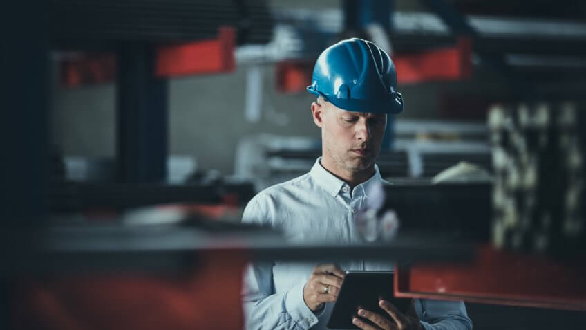 Male manager reading a plan on a touchpad while being in a warehouse.