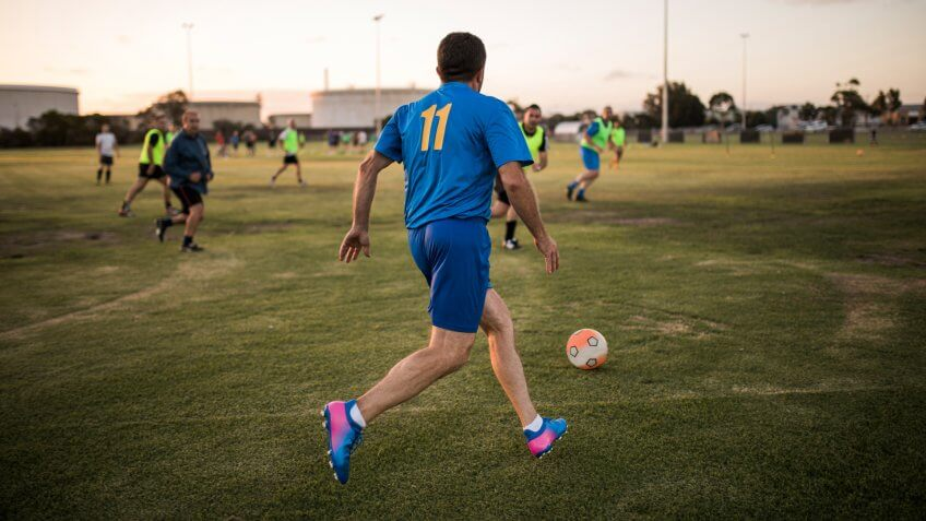 Male footballer lining up to kick the football.