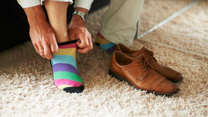 Man putting on colorful socks.