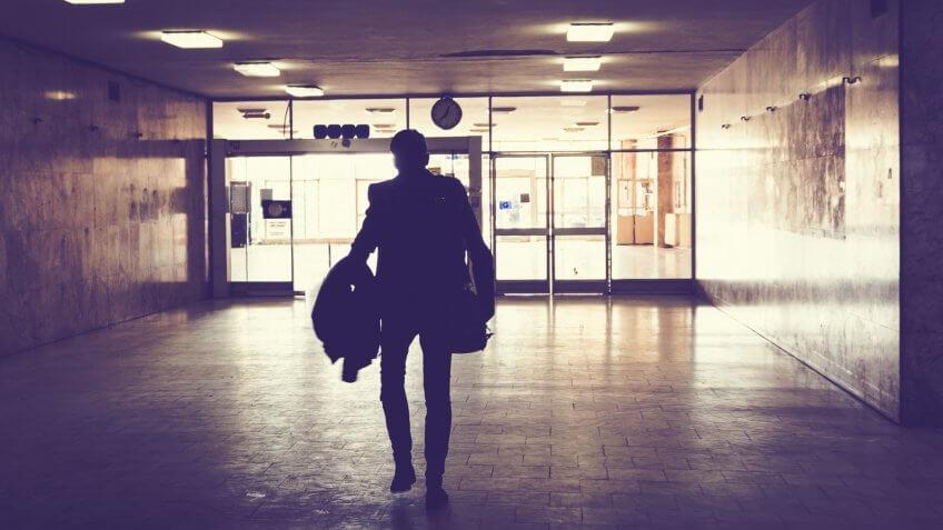 Rear view of man walking through dark corridor at rain station.