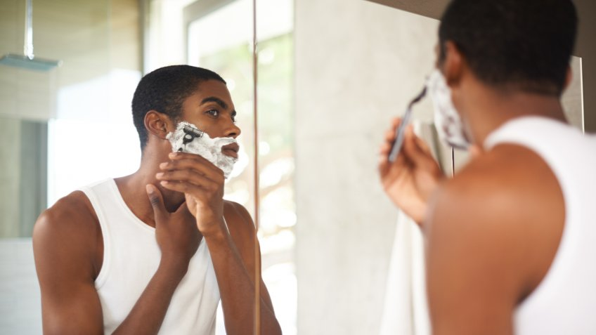 A young man shaving in the mirrorhttp://195.