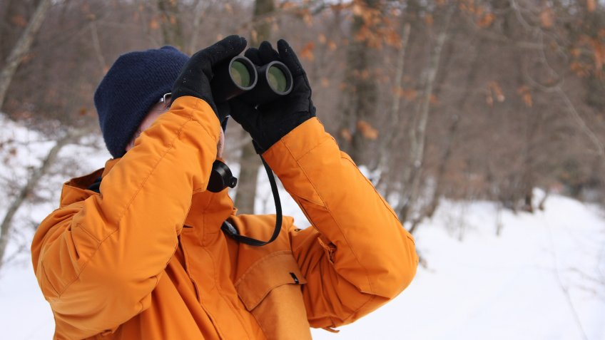 man using binoculars during winter