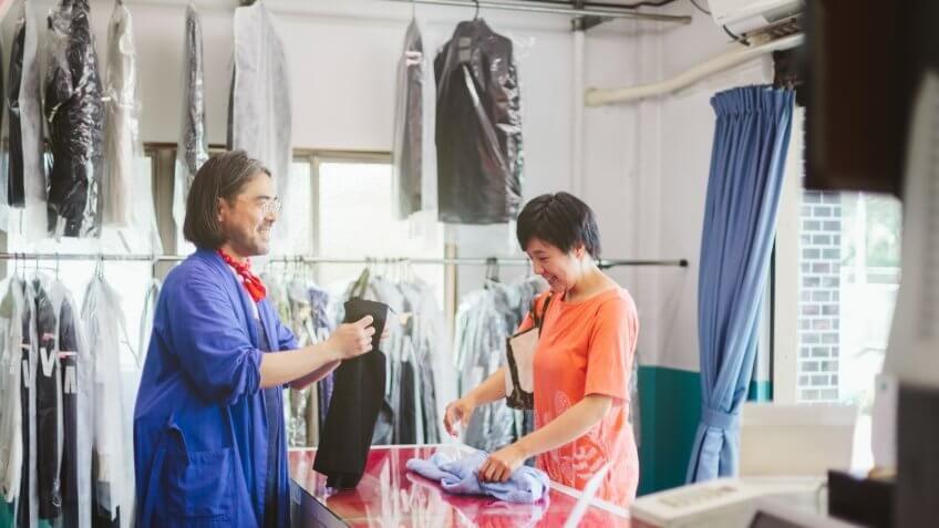 A man is taking clothes from a female customer for dry cleaning in a dry cleaning shop.