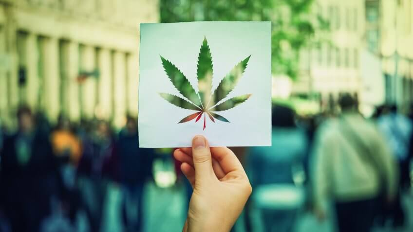 Hand holding a paper sheet with marijuana leaf symbol over a crowded street background.