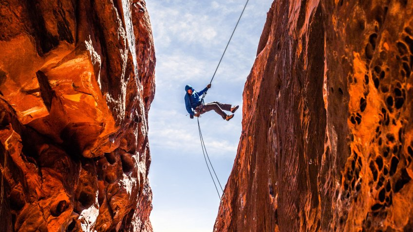 A rock climber kicks off the wall while descending into a slot canyon in Red Rock National Recreation Area.