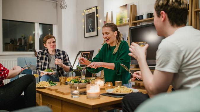 Two young couples are having a dinner party and one woman is laughing while serving salad.