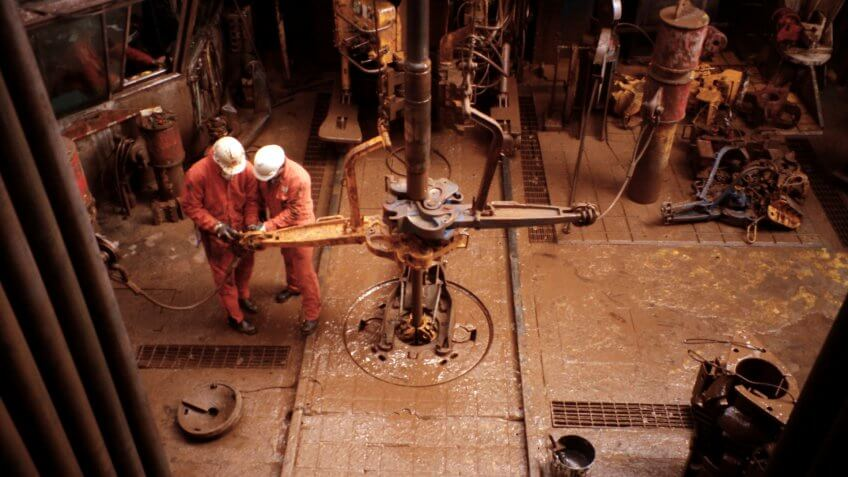 two roustabouts working on oil rig platform drill floor