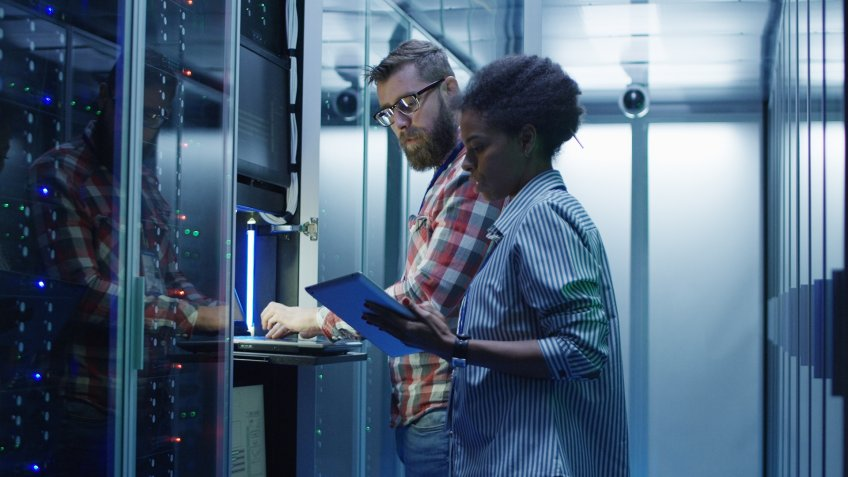 Modern multiethnic man and woman with tablet using laptop in server room while checking servers.