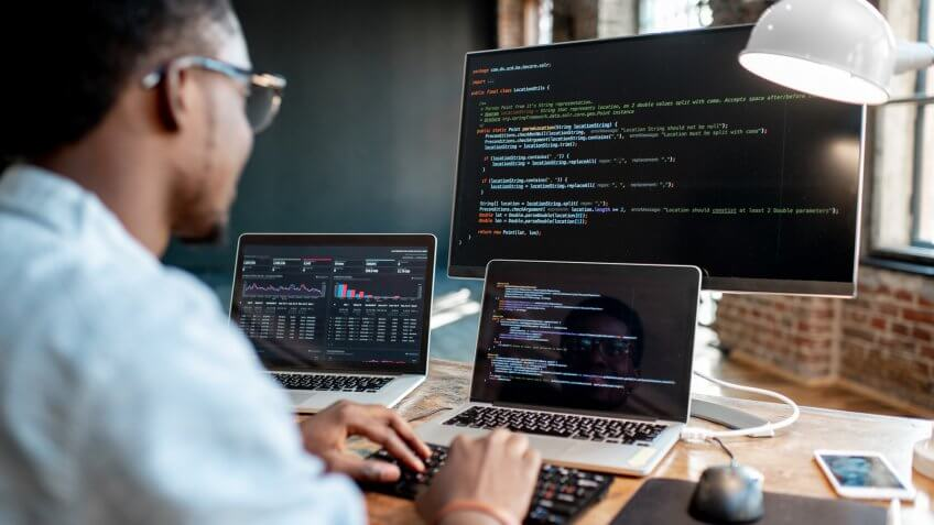 Young african male programmer writing program code sitting at the workplace with three monitors in the office.