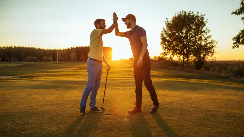 Shot of two golfers congratulating each other with a high five.