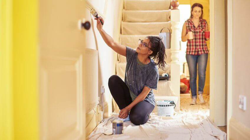 two women renovating their home giving it a fresh coat of paint