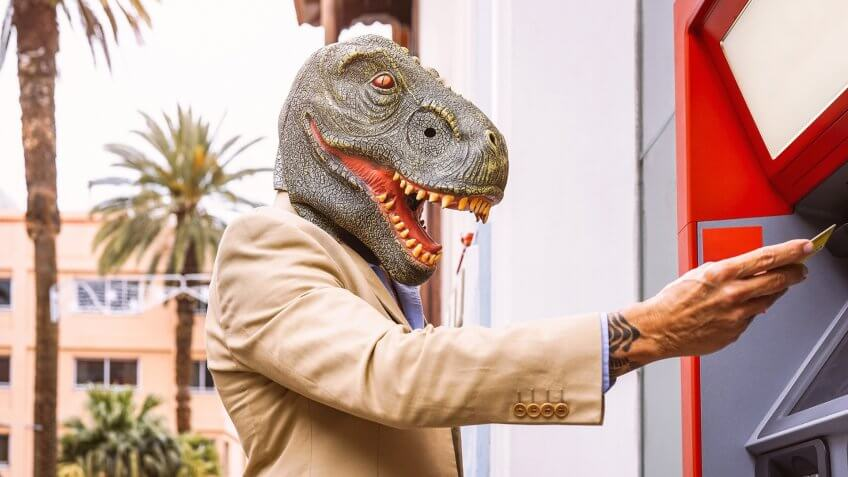 Senior man wearing t-rex dinosaur mask withdraw money from bank cash machine with debit card - Surreal image of half human and animal - Absurd and crazy concept of ATM advertise.