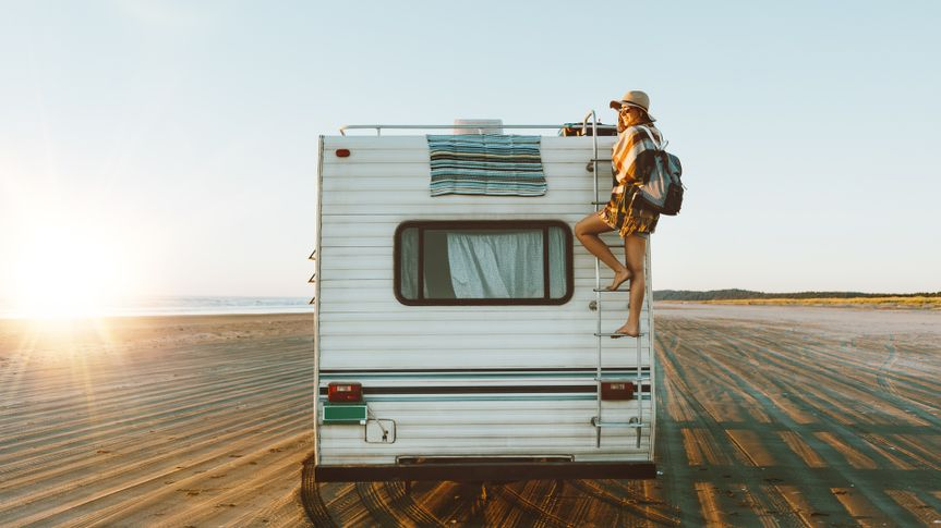 Charming young woman with nice smile with hat, sunglasses, backpack climing on recreational vehicle on the ocean beach at sunset.