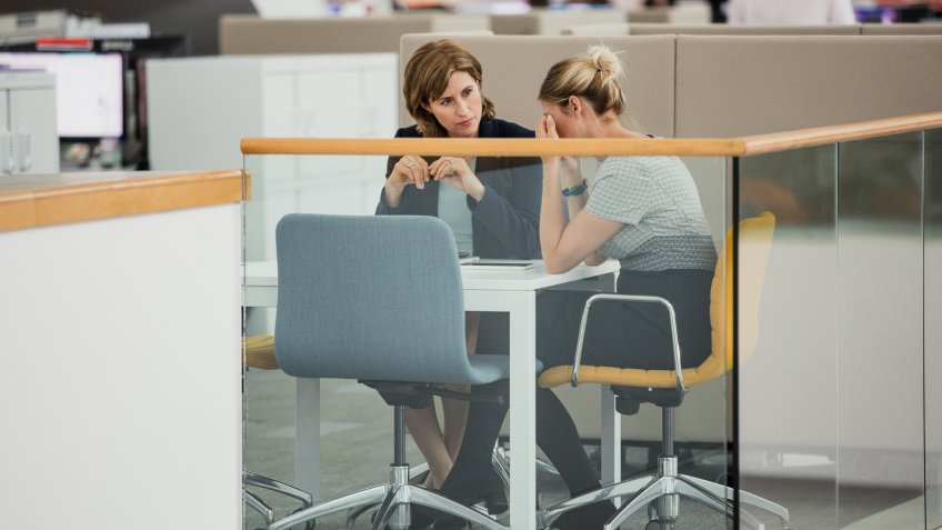 Two female colleagues having a meeting, one of them is upset.