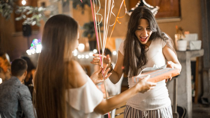 Woman welcoming guest on her birthday dinner party and receiving gifts.